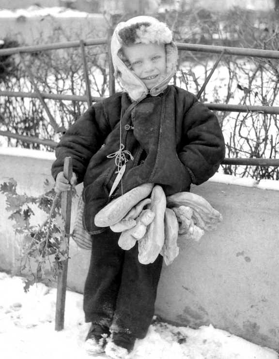 Boy stands with a string across his body. The ring-shaped loaves are thread through the string.