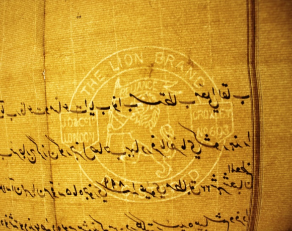 This image of the same letter from the Emir of Baghdad to the Lord Curzon, is now revealed under transmitted light, another technique of reading paper, to have a watermark, with a Lion holding a flag bearing the word 'Reliance' within a circular sigil entitled around the inner edge as 'The Lion Brand, Croxley number 693, London. some watermark text is obscured by the overwriting Arabic script.
