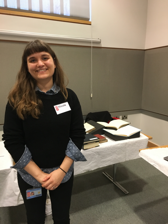 British Library Preventive Conservator Nicole Monjeau, standing in front of a display table bearing books, some resting on book supports.