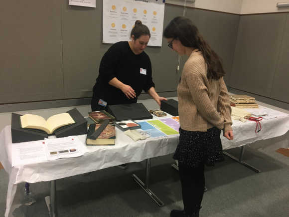 A PhD student stands in front of a display table manned by a Conservator, looking at the items on display promoting safe collection care, through coloured print outs and books with book supports.