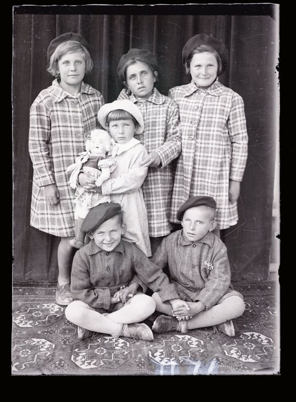 Portrait of children. Three older girls stand and wear identical coats. A younger child stands holding their soft doll and two boys sit on the ground (they also wear identical clothing and caps).
