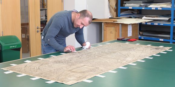 Rick Brown stands at a table which has a large map on top of it. Tabs of paper have been adhered around all four edges of the map, and Rick inspects an area.