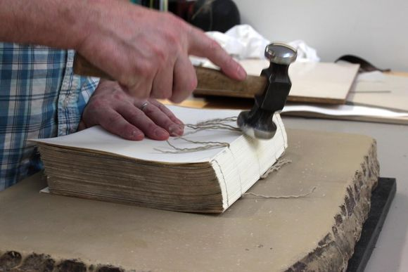 The sewn textblock rests on a lithography stone, while a conservator rounds the spine of the book by hitting it with a hammer.