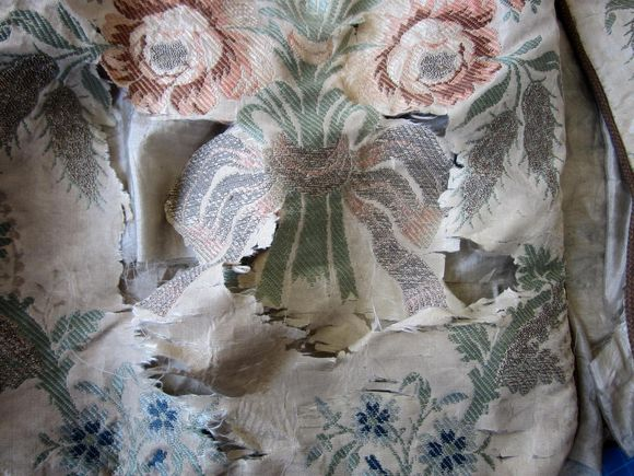 A close up of the mantle, which has a floral design on a cream background. There are a number of tears in the silk.