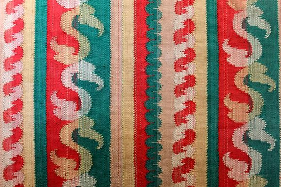 A closeup of the album's textile cover. There are vertical stripes of red, turquoise, and white with s-shaped flourishes.