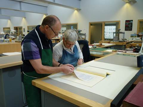 Two conservators inspect an item at the conservation bench.