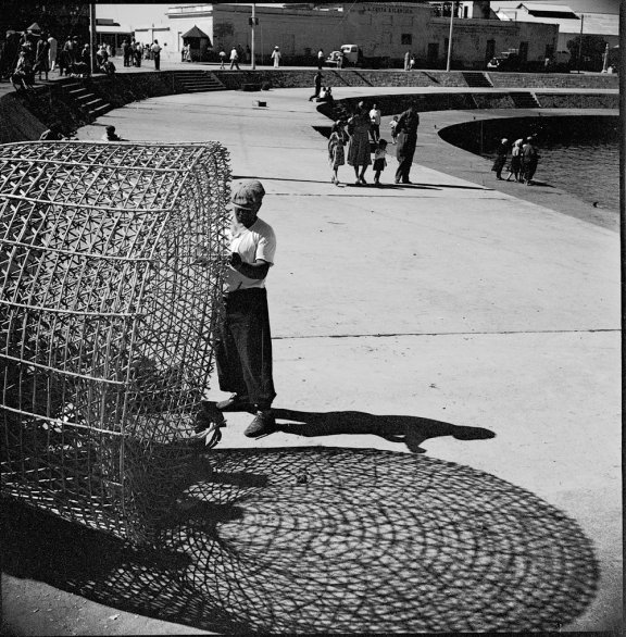 A man fixes a large fishing basket. It makes an attractive pattern on the ground.
