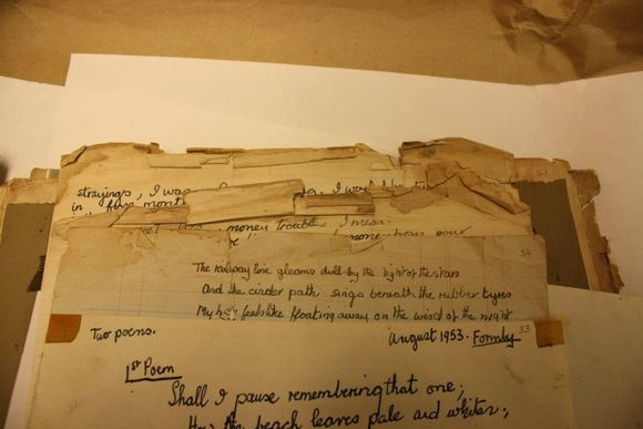 Varying scraps of paper rest on top of one another, with poems written on them. The papers are in generally poor condition with Selloptape present and the top edges crushed and torn.