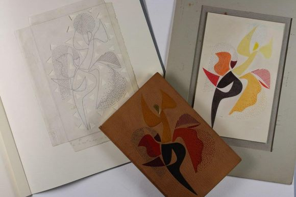 Varying stages of the final design, which is an abstract representation of a figure dancing, are laid out on a table. This includes a tracing, a drawing in colour, and the final design on leather.