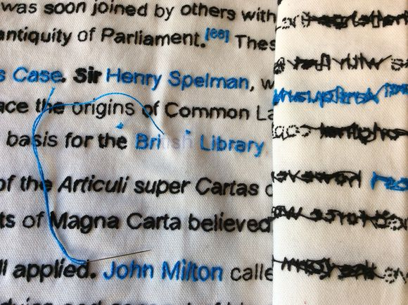A close-up of the words British Library which partially sewn in a blue thread, and a surrounded by other words mainly sewn in black thread.