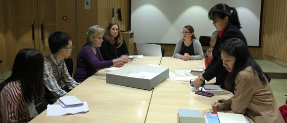 Eight colleagues sit around a table and discuss the oracle bones.