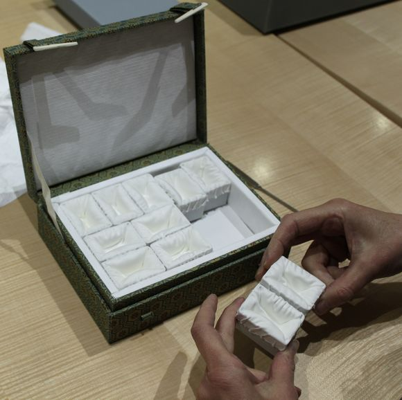A small ornate box with small individual compartments rests on a table, which someone holds two of the small individual compartments, which are covered in white silk.