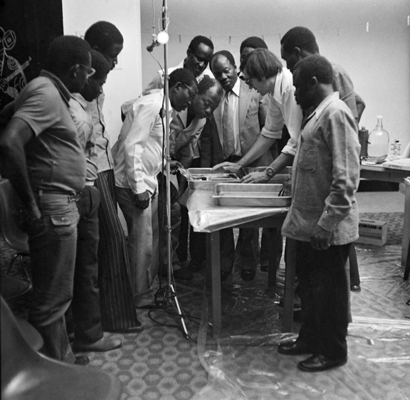 A group of men look at at a developer tray.