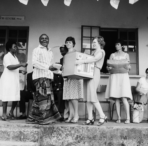 A group of people. One woman is carrying a large cardboard box.