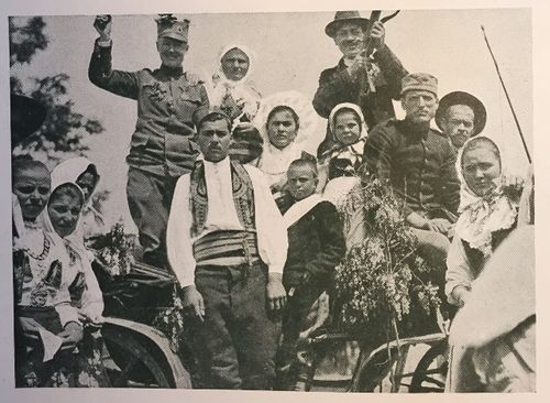 Flora Sandes standing on a cart with traditionally-dressed Serbs at a country wedding