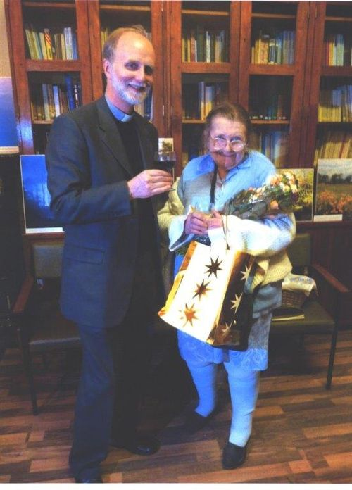 Photograph of Borys Gudziak presenting Vera Rich with flowers and a gift