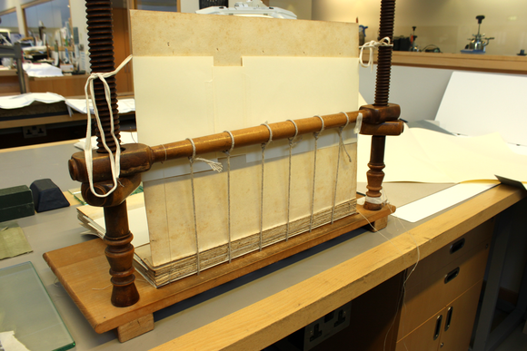 The textblock of the book sits on a sewing frame with six sewing stations as the book is resewn.