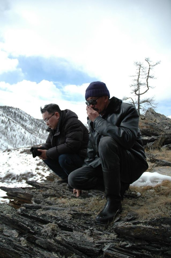 Two team members crouch down in the snowy landscape.