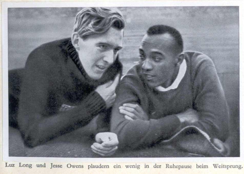 Photograph of Luz Long and Jesse Owens relaxing on the grass and talking