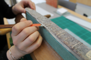 Camille inserts a scalpel into the spine of the book, starting the disbinding process.