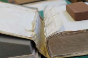 A close-up of the book showing the cover in the process of being reattached.