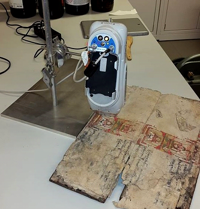 The manuscript sits below a p-XRF during testing.