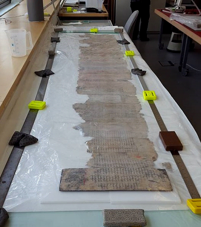 The manuscript lies unfolded on a table on top of humidified Gore-Tex and under polythene sheeting during humidification.