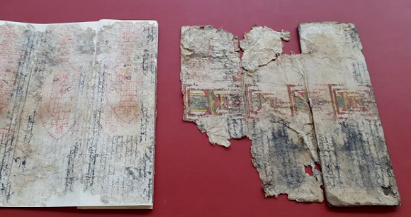 The two halves of the manuscript: one has undergone conservation treatment with its losses infilled, and the other half still showing losses and tears.