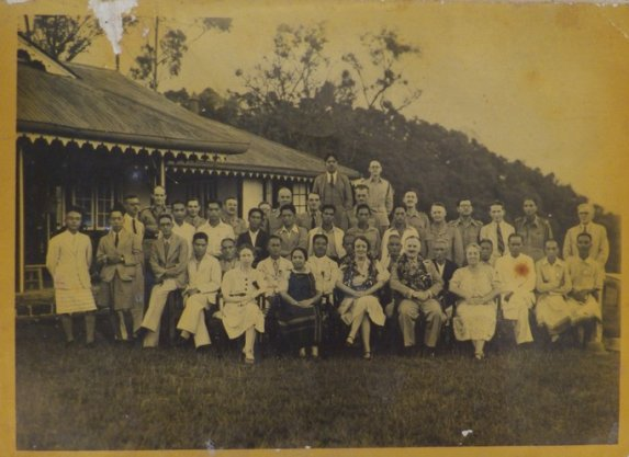 Group photograph with a bungalow to the left