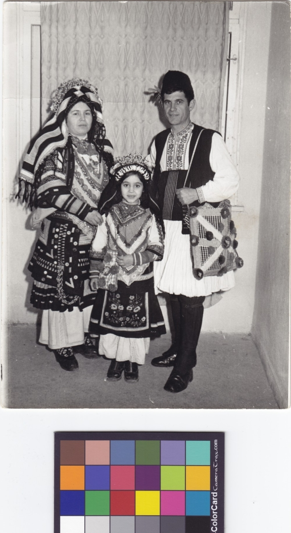 A couple and young girl all wearing traditional costume, pose for an informal photograph.