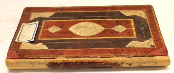 The Manuscript book photographed after conservation work. The book is lying down, with spine facing the camera. The spine itself has been reworked, with the linen backing and the remnants of leather spine well afixed and consolidated with toned Japanese tissue paper along the exposed linen backing of the spine.