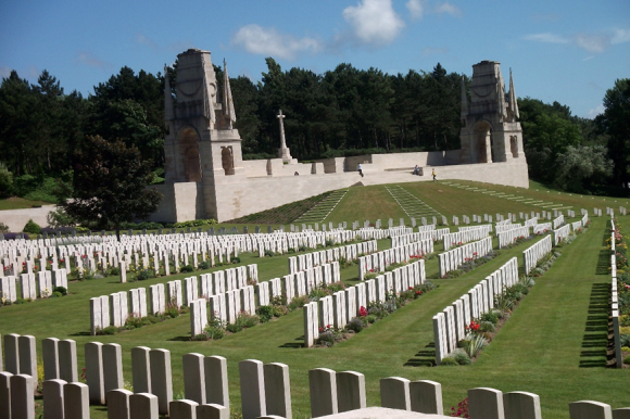 Etaples Military Cemetery with its rows of gravestones, green grass, and large building in the background.