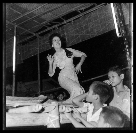 A female dancer with young boys watching.