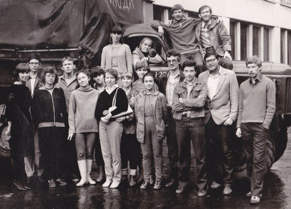 A group of young people standing by a truck.
