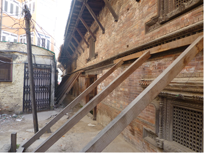 A courtyard sowing planks propping up the wall of the museum.