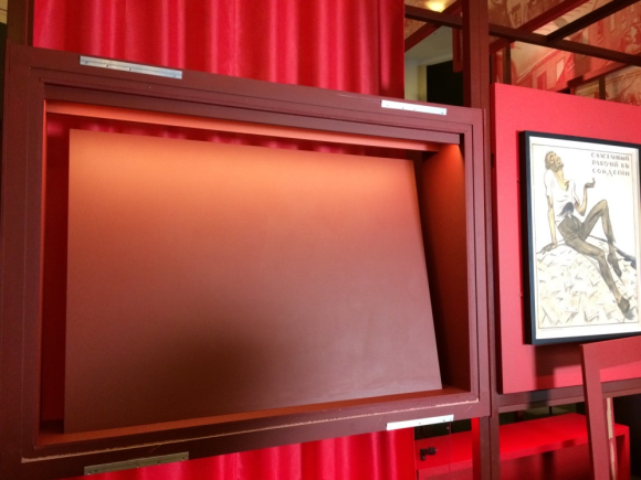 The display case ready to receive the banner. The case is square in landscape orientation, in a dull red colour. The backboard is manufactured to lean back on an angle to accomodate the flag at the right viewing angle. Next to the display case can be seen another print, of a man on a rock, already mounted.