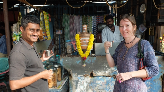 Ramesh Kumar and Zoe Headley on a tea break by a market stall.