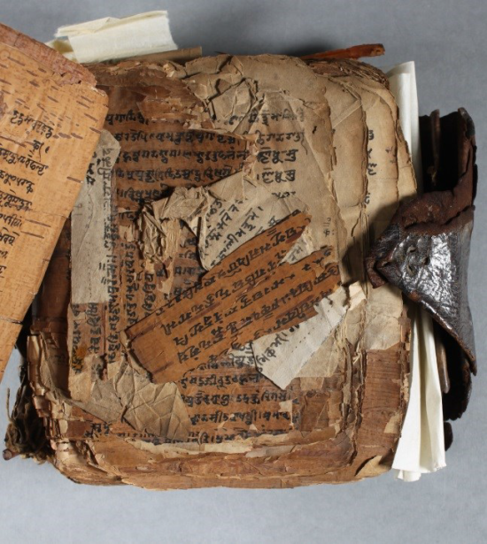 An open section of the manuscript, showing the fragmented sections which have broken away from their pages.