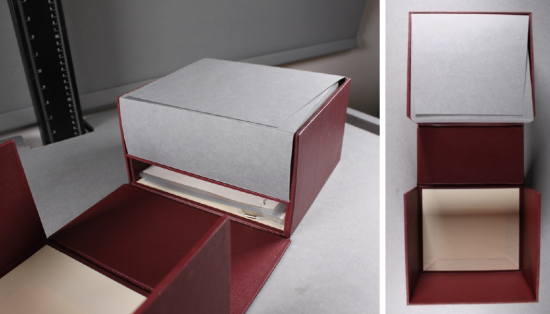 A drop-back box specially created for the manuscript. the outside is red buckram, while a grey card inner box sits inside, which will contain the manuscript and opens in a four-flap enclosure.