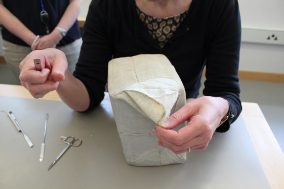 Liz Rose starts to unpick the stitches and open the parcel.