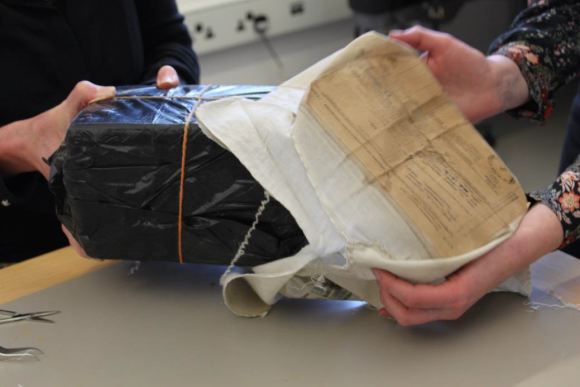 The parcel, wrapped in black and tied with string, being removed from the cotton wrapper.
