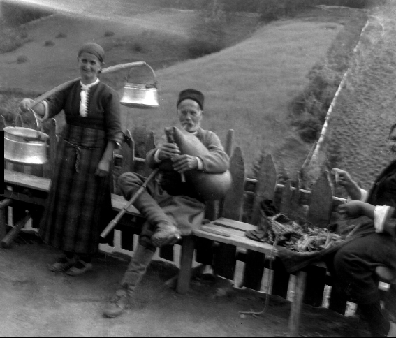Man sits playing the bagpipes, a woman carrying milk churns stands to the left.
