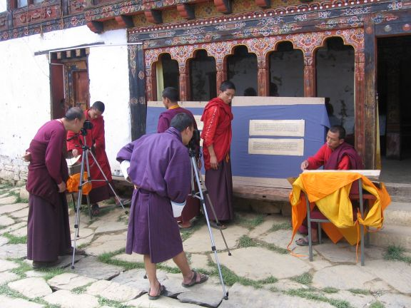 Monks digitising in the courtyard of a monastery.