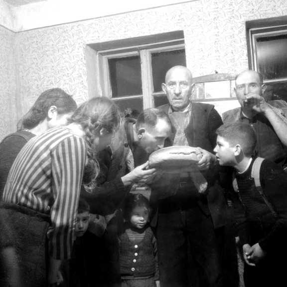 Photograph of a family standing around a loaf of bread.