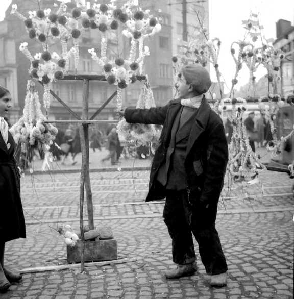 A boy touches a decorated stick.