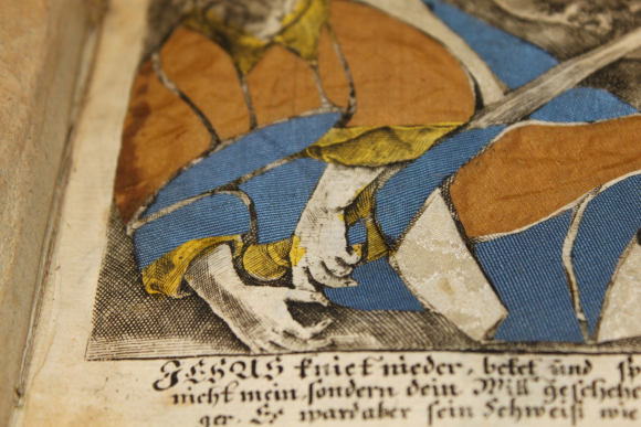A close up of the previous image, showing the blue and golden-brown textiles which are pasted onto the engraving image of the figure to the fore.Below the image is text in Gothic script, which clearly shows the name of Jesus at the start.
