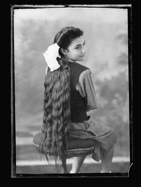Portrait of a young girl sitting on a stool. She has her back to the camera and her head is turned towards to right so she is in three quarter profile. Her long hair reaches past the seat of the stool.