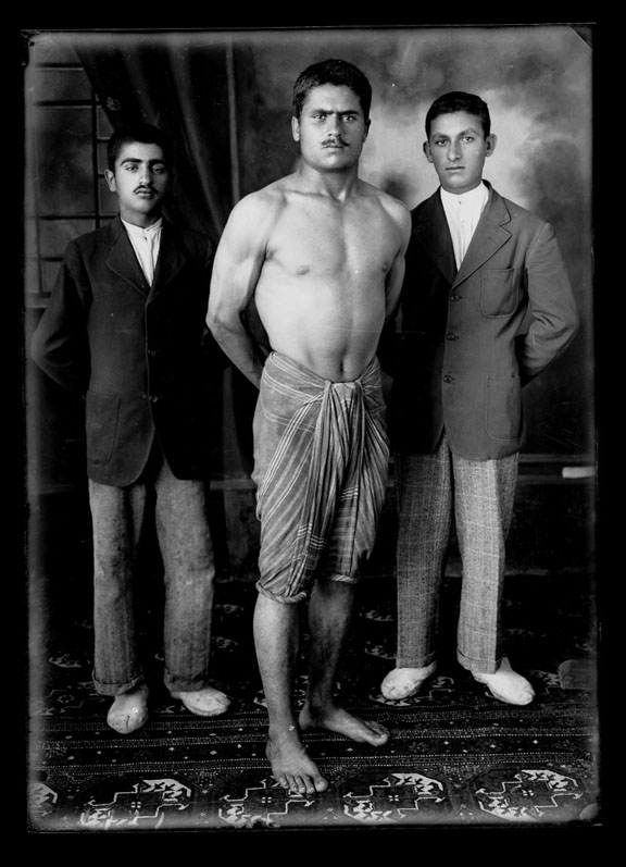 Three men stand looking at the camera. The central man, possibly a wrestler is barechested.