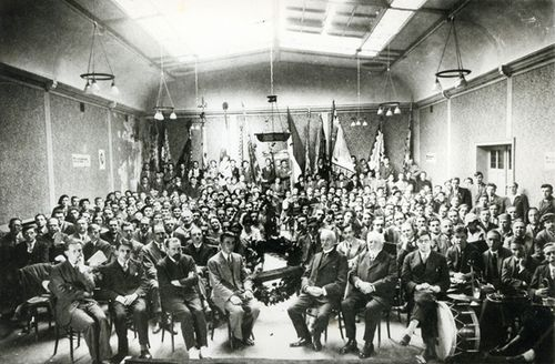 Photograph of delegates at a meeting of the at a meeting of the Algemeen Katholiek Vlaams Studentenverbond sitting in a large hall