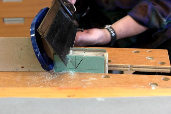 The book is placed in a wooden vice and a conservator uses a hand saw to cut out the triangular notch.